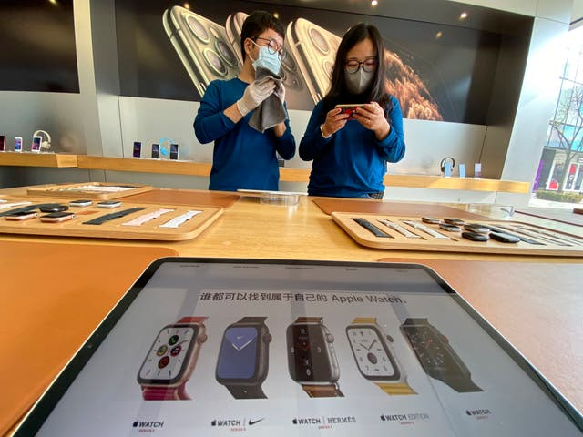 Workers wait for customers at an Apple retail store in Beijing, China
