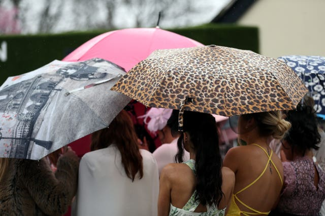 Racegoers accessorised with colourful umbrellas (David Davies/PA)