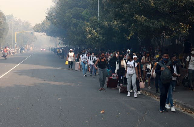 Students make their way after being evacuated from their residence at the University of Cape Town, South Africa