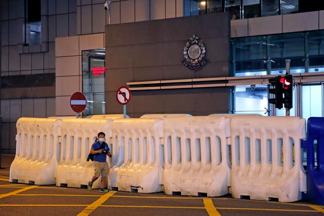 A journalist walks past the police headquarters in Hong Kong (Kin Cheung/AP)