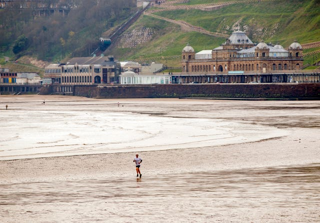 A man jogs on an empty beach in Scarborough during coronavirus restrictions in April (Danny Lawson/PA)