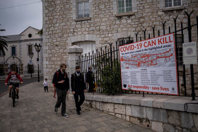 Schoolchildren walk by a Covid-19 informative banner in Gibraltar