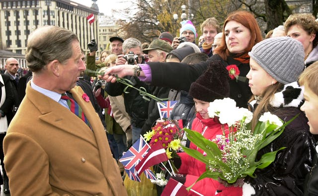 The Prince of Wales is slapped around the face with a flower by a war protester in Latvia (John Stillwell/PA)