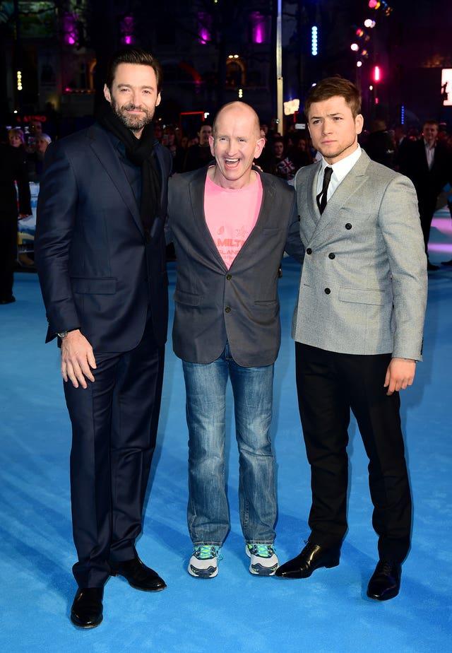 Hugh Jackman, left, Eddie Edwards, and Taron Egerton