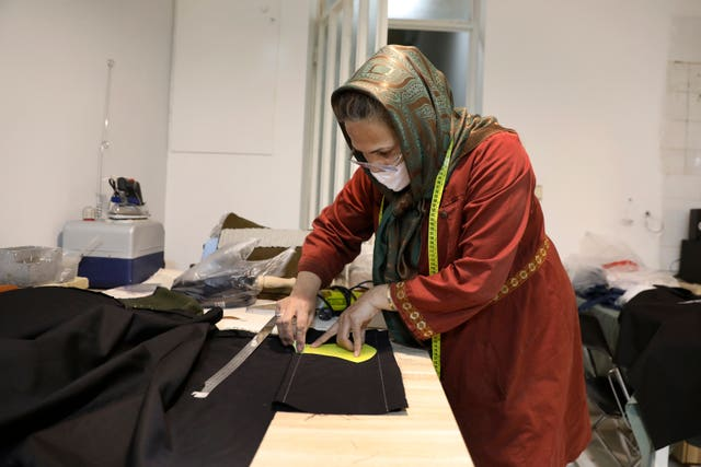 Fakhri Hashemian cuts fabric to sew a protective face mask at a workshop of Bavar charity in Tehran, Iran