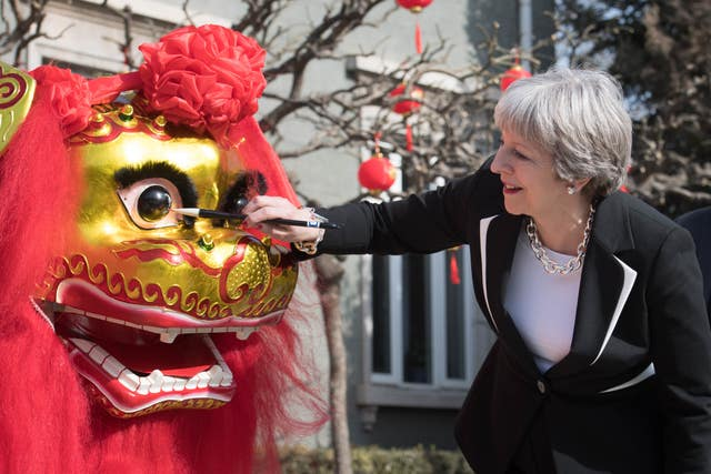 The PM 'dots the eye' of a Chinese dragon in the grounds of the British Embassy
