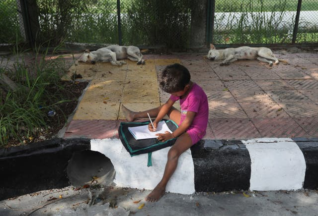 A child practices writing during a pavement class taught by an Indian couple, Veena Gupta and her husband Virendra Gupta, in New Delhi, India