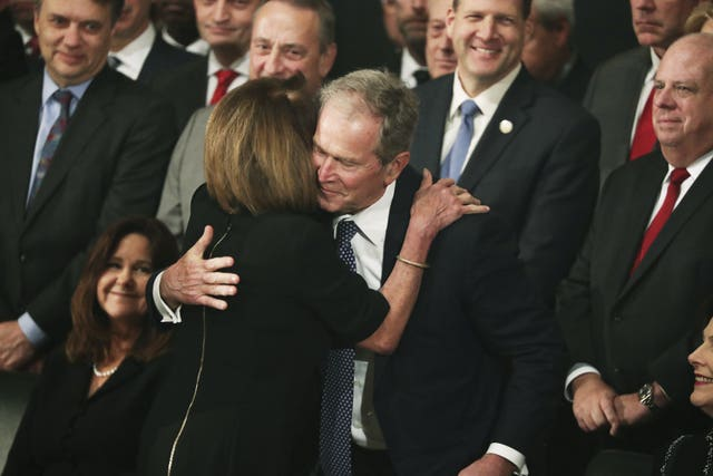 Former President George W Bush is embraced by Democratic House leader Nancy Pelosi