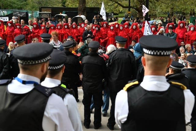 Police guard protesters outside the Treasury in Westminster, London, during an Extinction Rebellion (XR) climate change protest. (Dominic Lipinksi/PA)