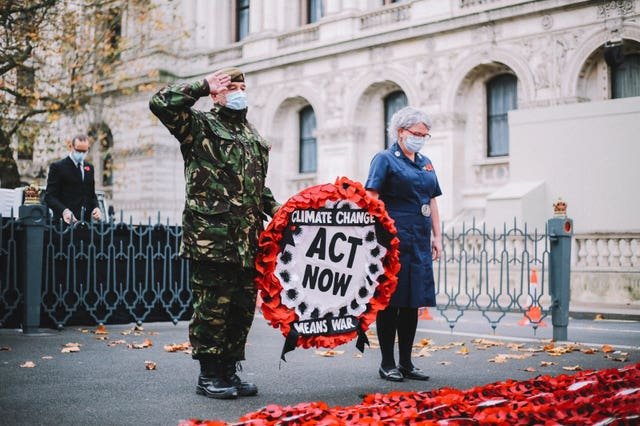 Extinction Rebellion campaigner Donald Bell observed a two-minute silence before hanging a wreath of poppies on the Cenotaph