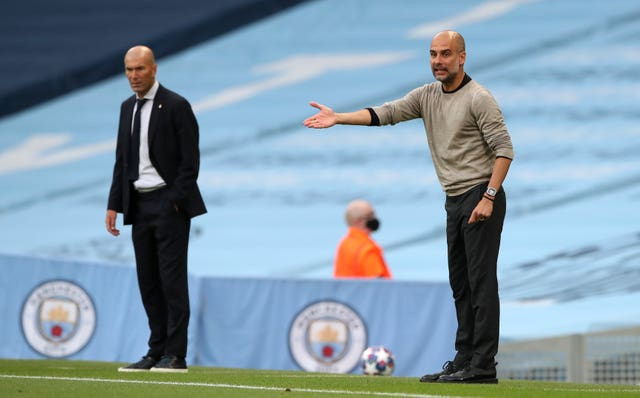 Pep Guardiola gestures on the sideline, alongside Real Madrid manager Zinedine Zidane and a Champions League ball