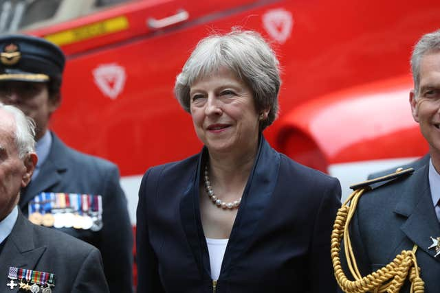 Prime Minister Theresa May stands with members of the RAF in front of a replica of a Hawk jet (Jonathan Brady/PA)
