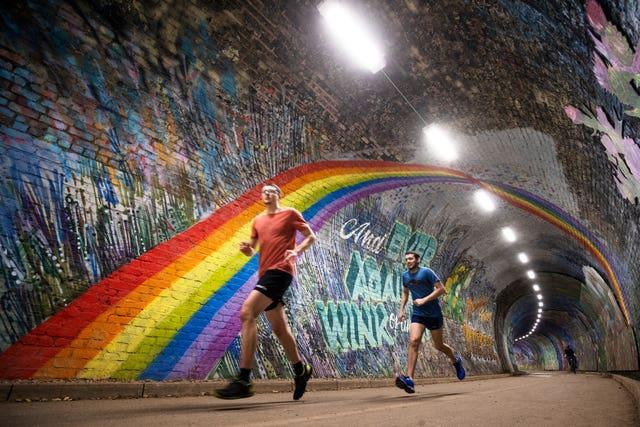 People jog through tunnel