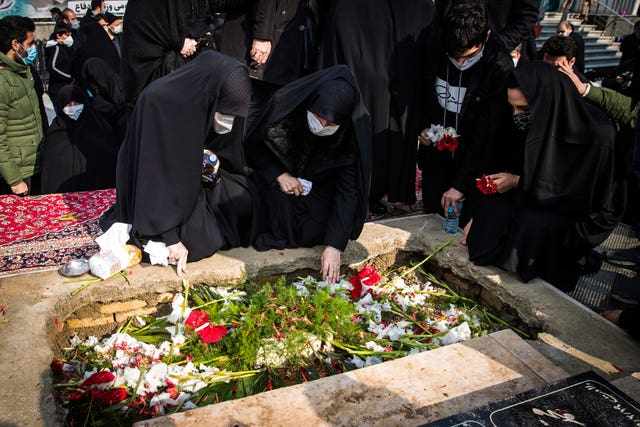 People pray at the grave of Mohsen Fakhrizadeh, a nuclear scientist who was killed (Hamed Malekpour/AP)