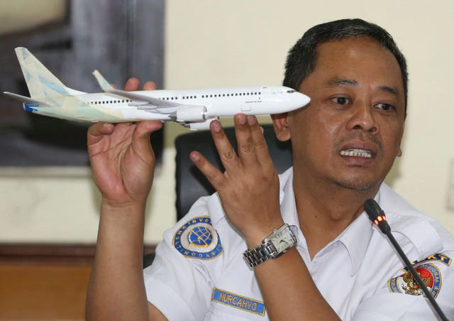 National Transportation Safety Committee investigator Nurcahyo Utomo holds a model of an airplane during a press conference on the committee's preliminary findings on their investigation on the crash of Lion Air flight 610