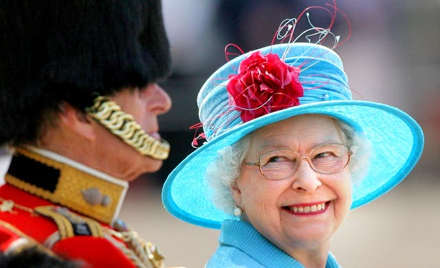 The Queen, in blue for a Trooping the Colour parade, smiling at the Duke of Edinburgh (Lewis Whyld/PA)