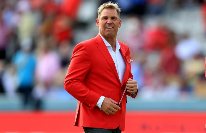Australian pundit Shane Warne wearing a red blazer on the Lord's pitch