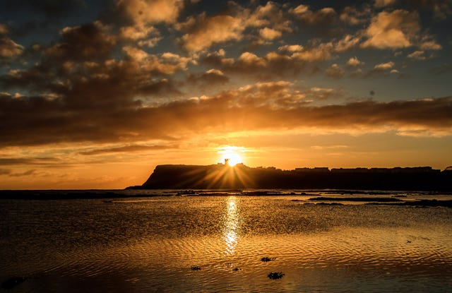 The sun rises behind Scarborough Castle in Yorkshire (Danny Lawson/PA)