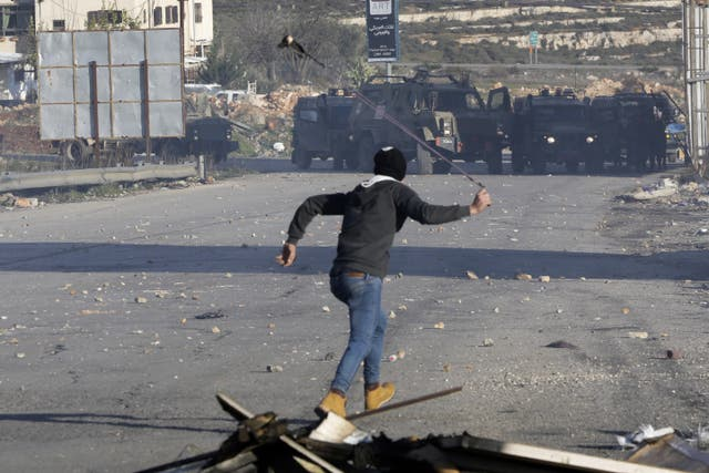 A Palestinian protester faces Israeli troops near Ramallah