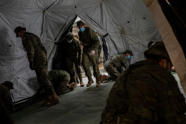 Spanish soldiers erect a tent to be used by patients