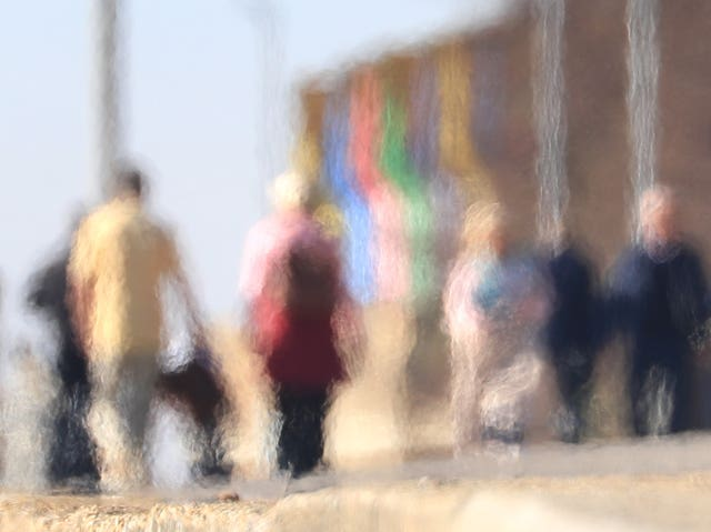 People are seen through a heat haze walking in the sunshine in Kent