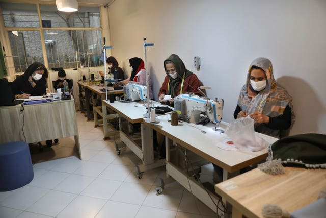 Women sew protective face masks at a workshop of Bavar charity in Tehran, Iran