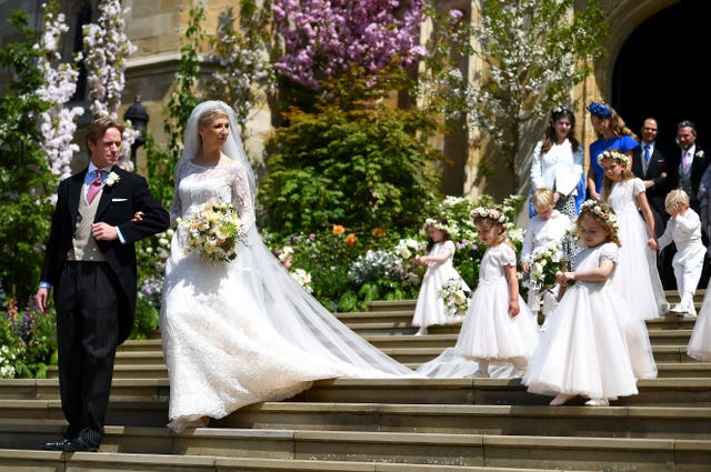 The couple leaving the chapel with the bridal party (Victoria Jones/PA)