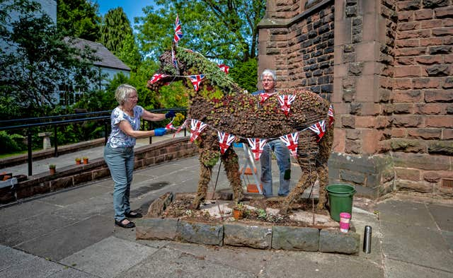 Wendy Doig and Roy Barker from St James Church in Woolton Village dress Jimmy the War Horse ahead of VE Day celebrations