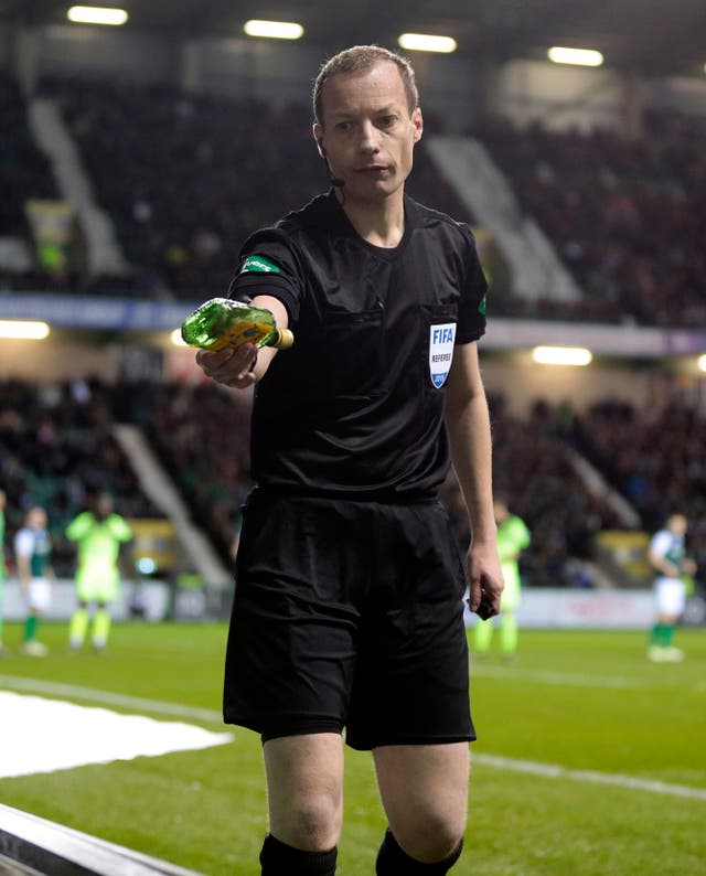 Referee Willie Collum removes a bottle from the pitch during Hibernian's clash with Celtic