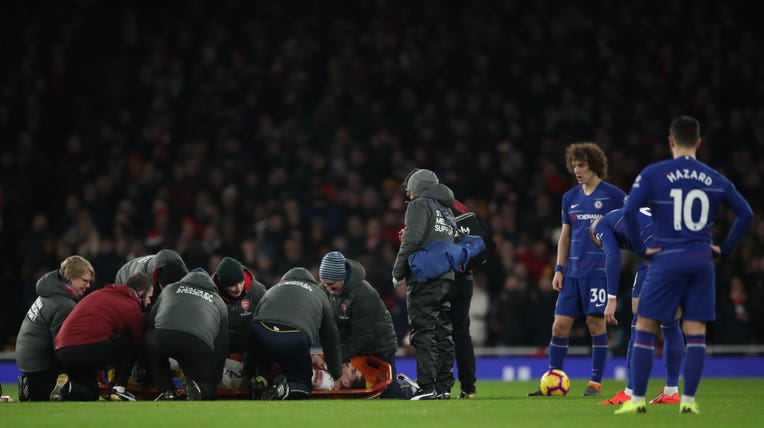 Bellerin is tended to by medical staff after suffering a knee injury against Chelsea in January of this year