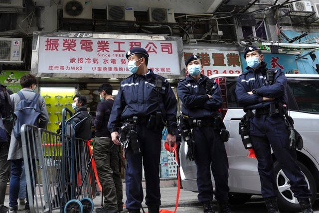 Police officers stand guard outside the office of district councillor and lawyer Daniel Wong Kwok-tung in Hong Kong
