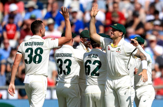 Australia's Josh Hazlewood (left) celebrates taking the wicket of England's Joe Root