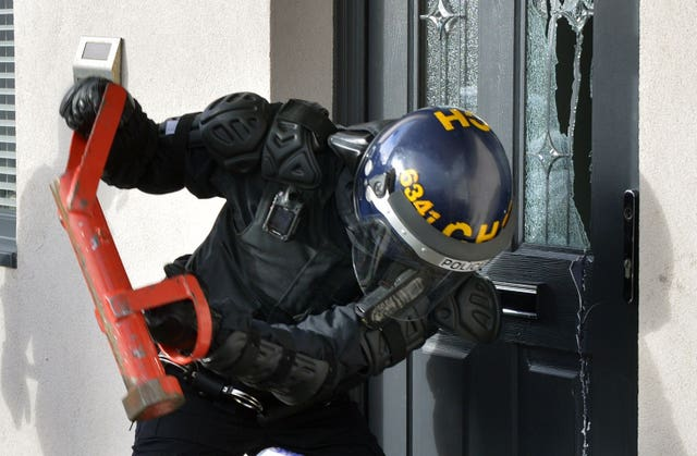 Police carrying out a raid during a crackdown on county lines drugs gangs