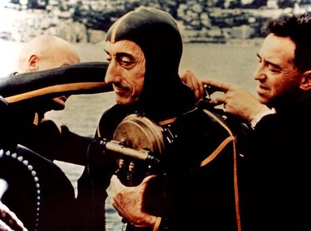 Jacques Cousteau putting his gear on