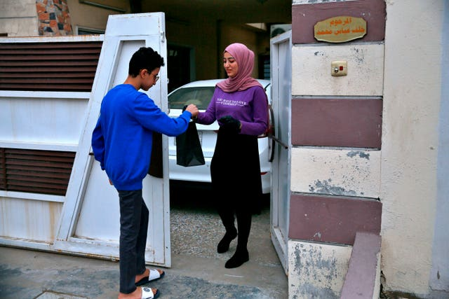 Fatima Ali hands her takeaway cheese-plate to a customer in Baghdad, Iraq