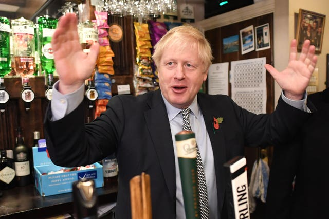 Prime Minister Boris Johnson steps behind the bar to pull a pint as he meets with military veterans at the Lych Gate Tavern in Wolverhampton