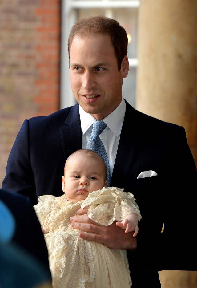 The Duke of Cambridge arrives, holding his son Prince George, at Chapel Royal in St James's Palace, ahead of the christening (John Stillwell/PA)
