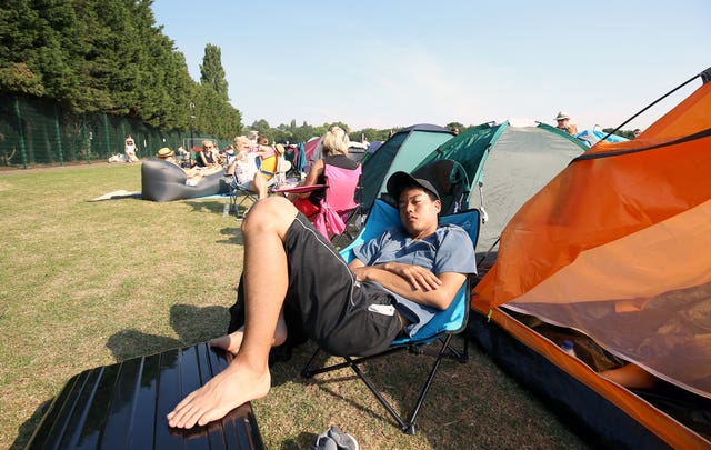 A spectator relaxes in the queue at the start of day five of Wimbledon 2018