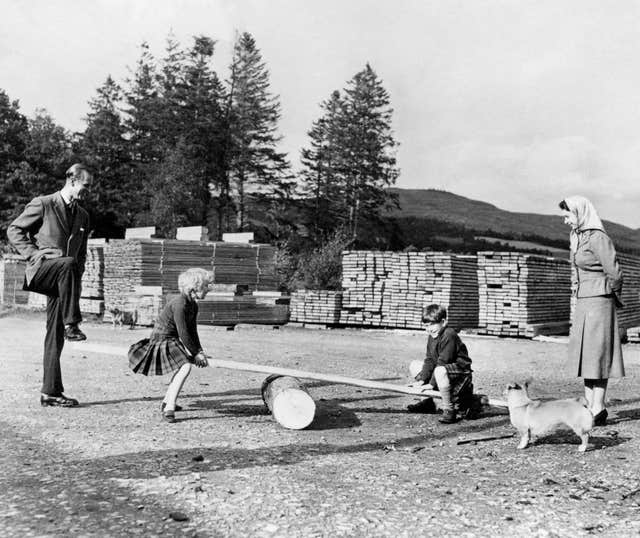 Prince Charles and Princess Anne, watched by the Queen and the Duke of Edinburgh, play on a see-saw made from a log and a plank of wood on the Balmoral Estate in 1957