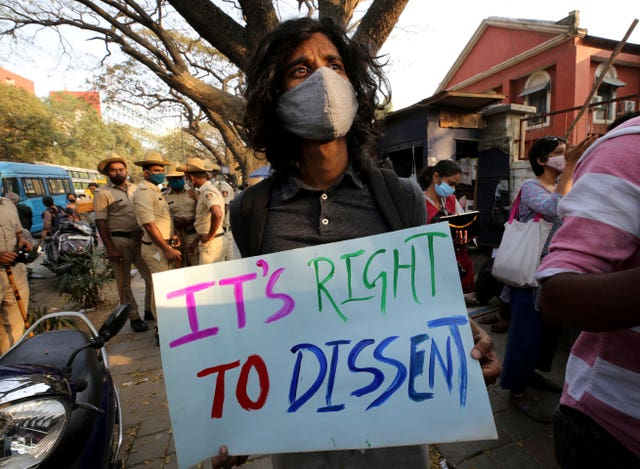 A man holds a placard demanding the release of Indian climate activist Disha Ravi during a protest in Bengaluru