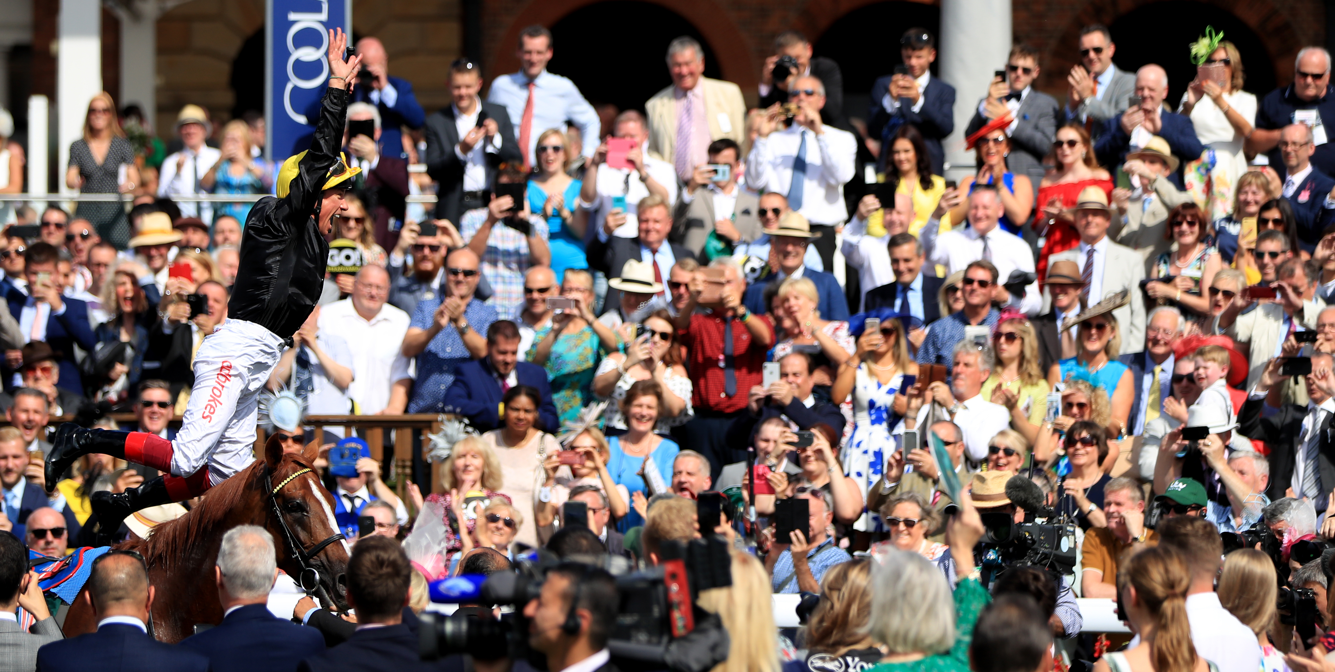 Frankie Dettori delights the crowd with his customary flying dismount after the victory of Stradivarius in the Weatherbys Hamilton Lonsdale Cup