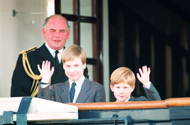 Prince William, nine, and his younger brother Prince Harry, seven, wave to photographers as they board the Royal Yacht Britannia (Martin Keene/PA)