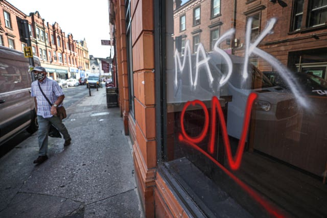 "A man wearing a face covering walks past graffiti with the slogan ""Mask On"" covering a vacant shop window in the High Street in Worcester, some six months on from the evening of March 23 when Prime Minister Boris Johnson announced nationwide restrictions"