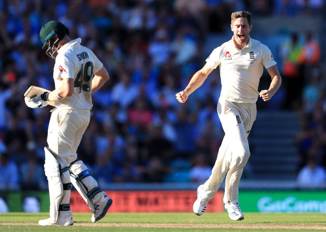 Chris Woakes, right, celebrates taking the wicket of Steve Smith