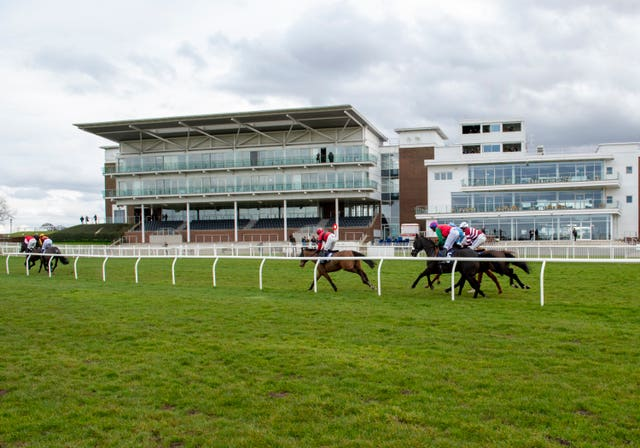Runners and riders pass the empty stands at a race meeting at Wetherby on Tuesday