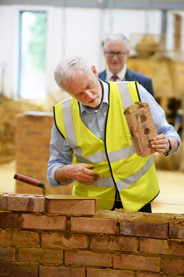 Labour leader Jeremy Corbyn tries bricklaying (John Stillwell/PA)