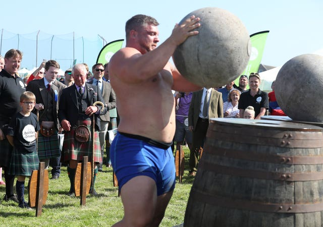 Charles watched on as strongman Luke Stoltman lifted heavy stones onto barrels