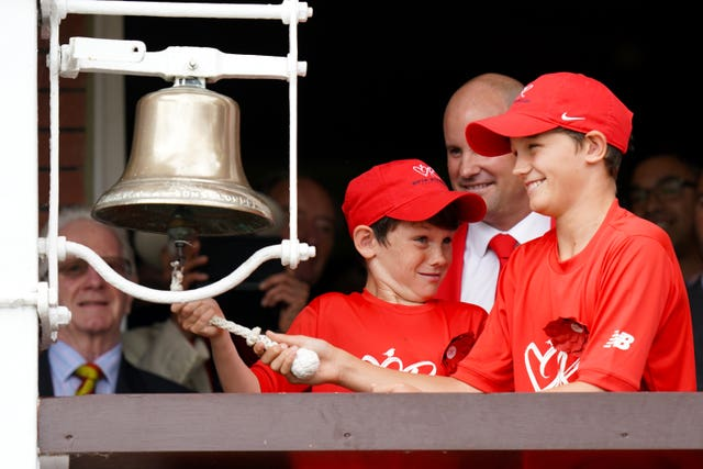Andrew Strauss watches his sons ring the bell