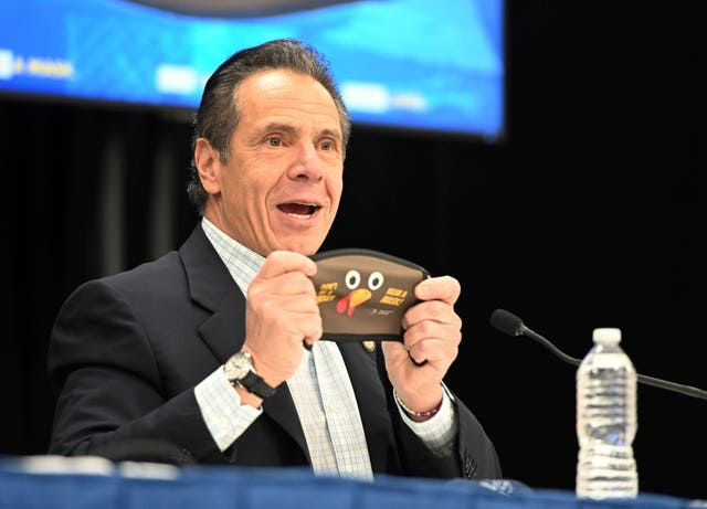 New York governor Andrew Cuomo holds up a new Thanksgiving-themed face mask (Kevin P. Coughlin/AP)
