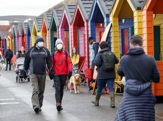 People wear face masks as they walk past beach huts in Saltburn-by-the-Sea